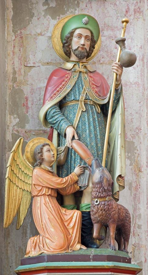 Mechelen - den sned och polychromed statyn av st Roch kyrktar in vår dam över de Dyle royaltyfria bilder