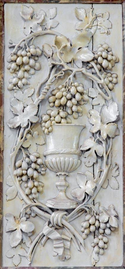 Mechelen - geschnitzte Entlastung der Kappe als Symbol des heiligen Abendmahl und des Bluts von Jesus Christ in der Kirche unsere stockfotografie