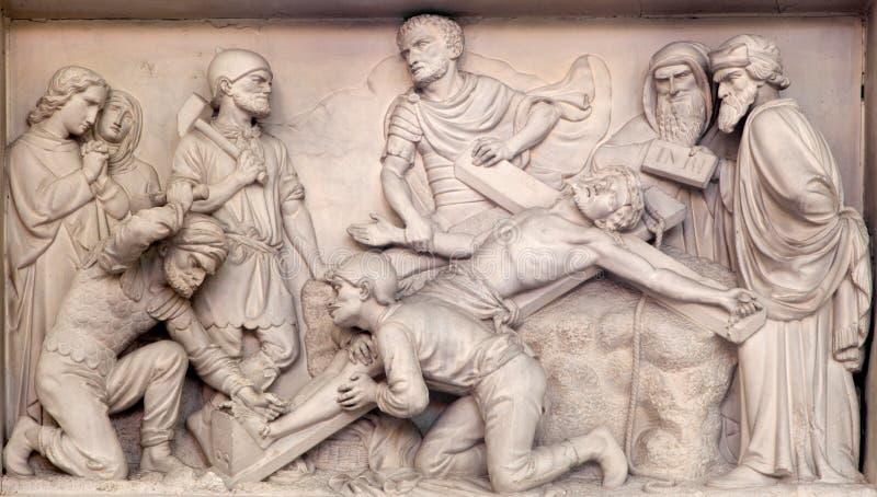 Mechelen - Kamienny reliefowy Jeus przybija krzyż w kościół Nasz dama przez De Dyl zdjęcie royalty free