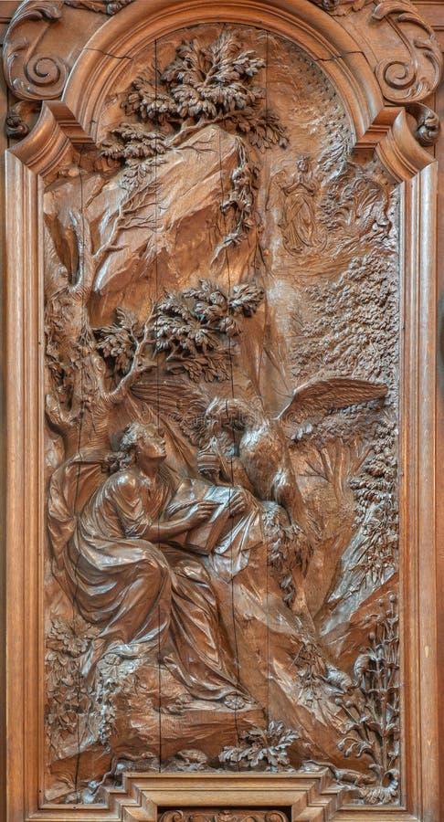 Mechelen - Rzeźbiąca ulga Writing ewangelia święty John ewangelista Ferdinand Wijnants w st Johns kościół zdjęcie stock