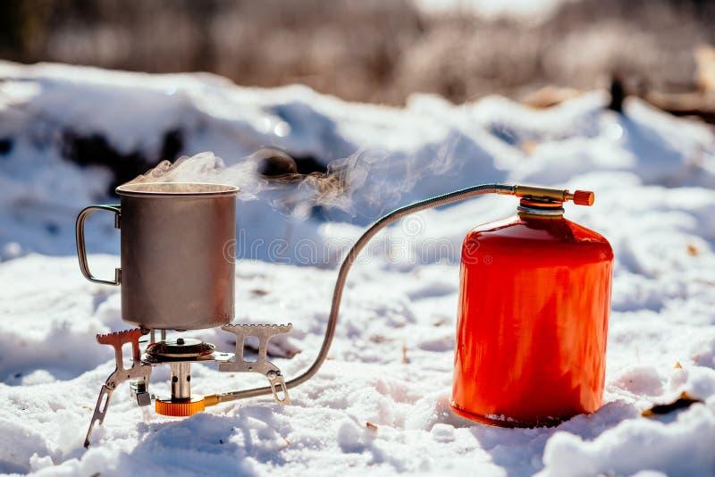 Mechero de gas portátil en un bosque Bushcraft del invierno, la caza y p imagen de archivo