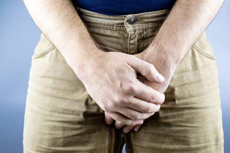 Med båda händer stänger mannen ljumsket från slaget, gul jeans royaltyfri foto