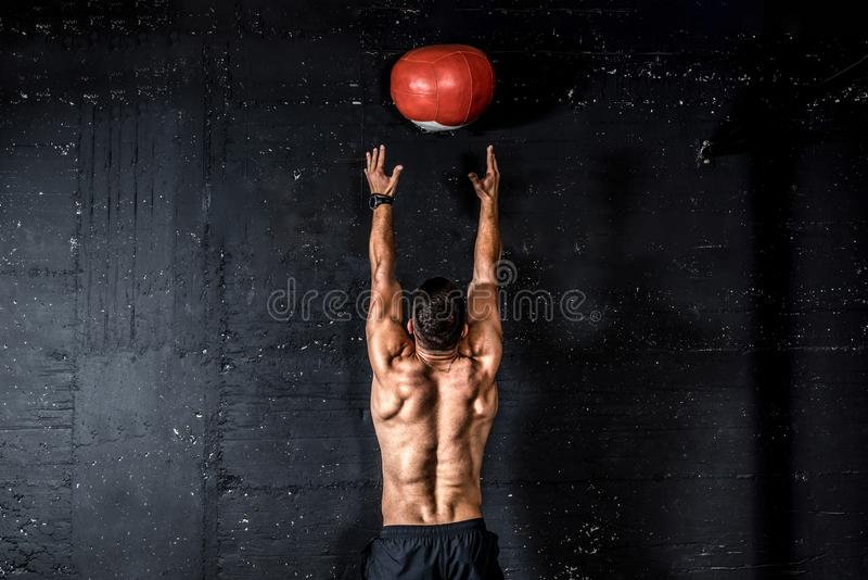 Young strong sweaty focused fit muscular man with big muscles doing throwing medicine ball up on the wall for training hard core w. Med ball throw, Young strong stock photography
