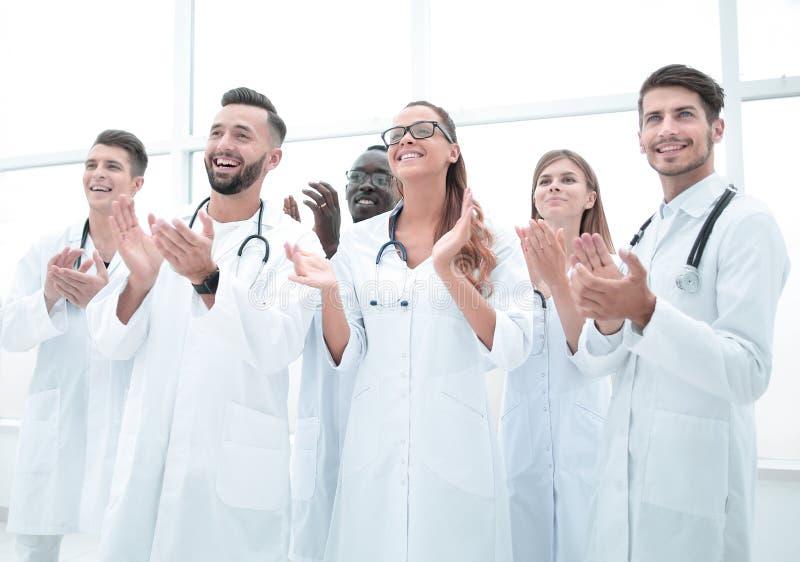 Med- doktorer applåderar och ler fotografering för bildbyråer
