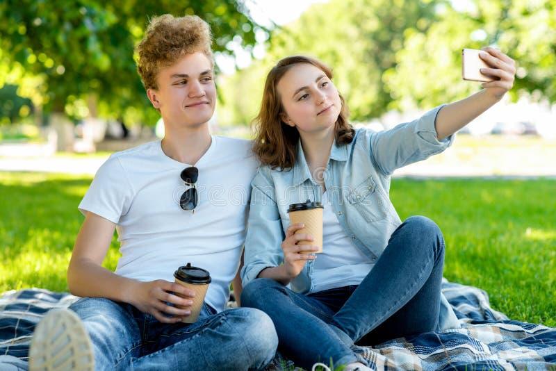 Med en flicka i sommar i natur De sitter på en filt Han rymmer koppar med kaffe eller te i hans händer Han tar bilder royaltyfri bild