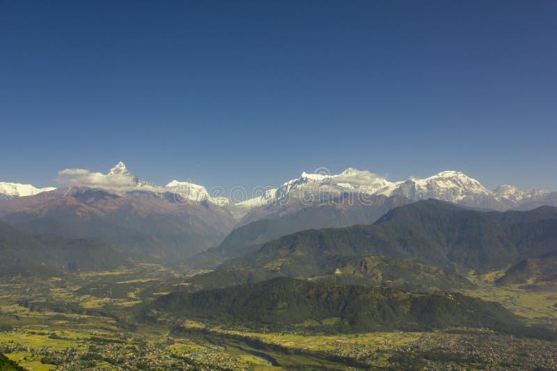 By med en flod i en grön bergdal mot de skogsbevuxna lutningarna och de snöig maxima av Annapurn i vita moln under en blått royaltyfria foton