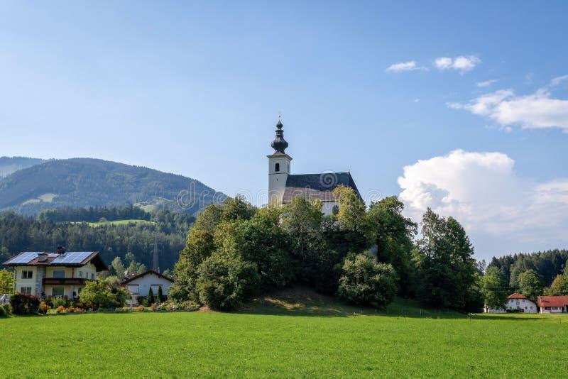 By med en kyrka i den alpina dalen nära Salzburg r arkivbilder