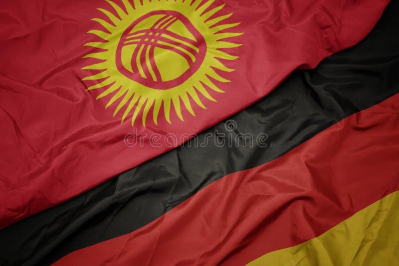 med färglös flagg från Tyskland och nationalflagg från kyrgyzstan arkivfoto