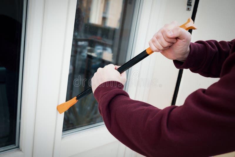 Med huva inbrottstjuv som tvingar fönsterlåset för att göra en stöld i ett hus royaltyfri fotografi