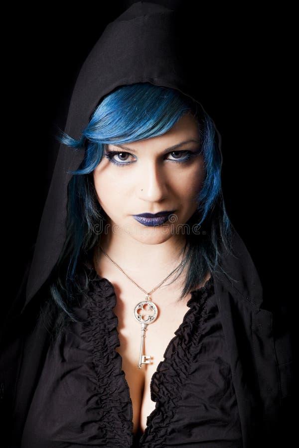 Med huva mörk kvinna med blå hår och läppstift Nyckel- hänge royaltyfria bilder