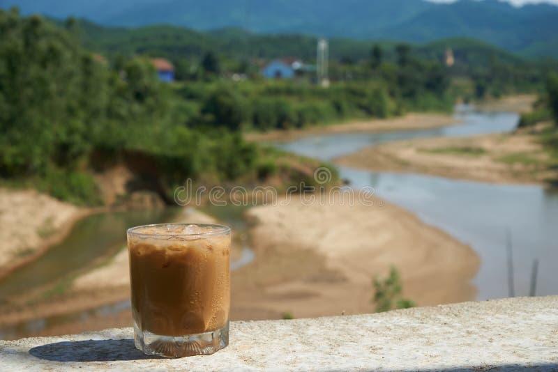 Med is kaffe eller caffelatte framme av ett trevligt suddigt landskap i Vietnam, Phong NhaKe smäll Nationalpark royaltyfri foto