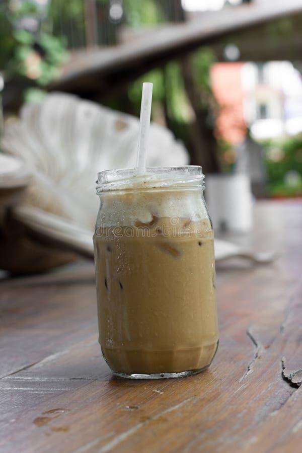 Med is kaffe med mjölkar är på tabellen royaltyfri foto
