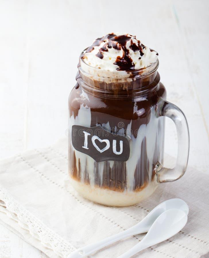 Med is kallt kaffe, frapuccino med piskad kräm och chokladsirap i krus royaltyfria foton