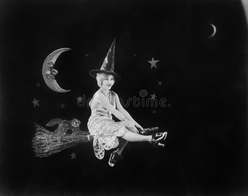 Med mannen i månen och en häxa på en kvast tänder ett flyg av fantasin natthimlen (alla visade personer inte är längre li royaltyfri fotografi