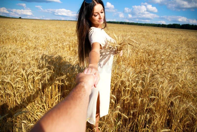 Med mig, kommer den unga härliga flickan rymmer handen av en man i ett vetefält arkivbilder