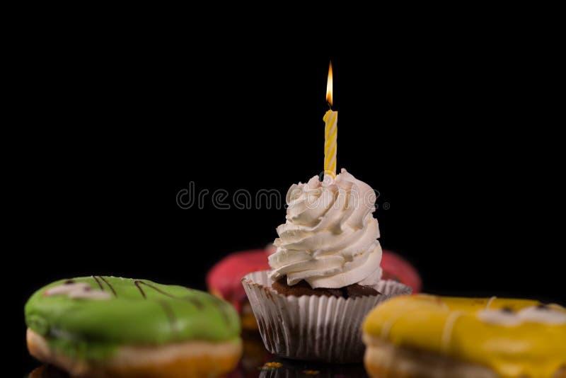 Med is muffin med den snurrade isläggning och stearinljuset fotografering för bildbyråer