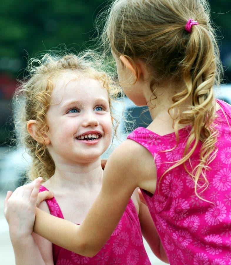 med tillbedjan flicka henne lilla systerleenden royaltyfri bild
