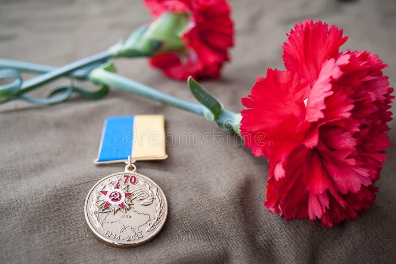 Medaglia 70 anni di liberazione dell'Ucraina dai Nazi e da due garofani rossi fotografia stock