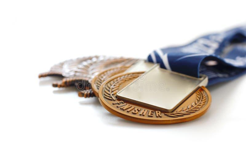 Medaglia d'oro su fondo bianco, sul concetto per la conquista o sul successo immagini stock libere da diritti