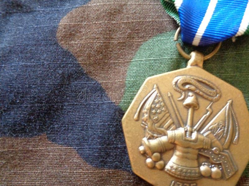 Medaglia di risultato dell'esercito sull'uniforme del cammuffamento del terreno boscoso fotografia stock
