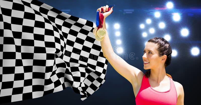 Medaglie della tenuta dell'atleta contro la bandiera a quadretti in stadio immagine stock