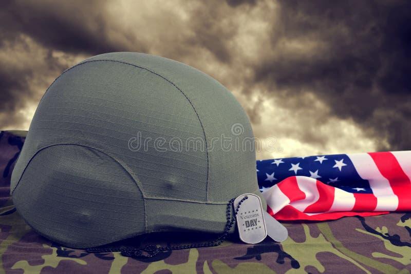 Medagliette per cani, casco e bandiera americana sul tessuto del cammuffamento fotografie stock libere da diritti