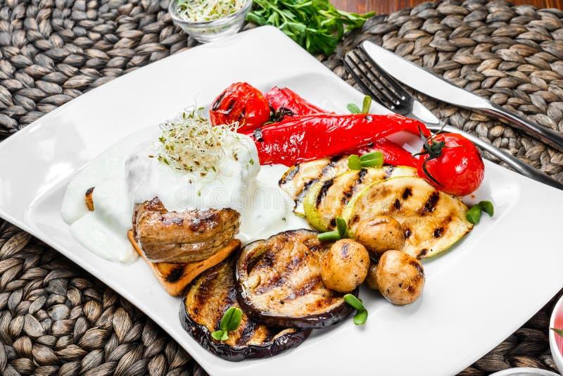 Medaglione arrostito del vitello della bistecca della carne con la salsa di formaggio e le verdure al forno sul piatto Alimento s fotografia stock