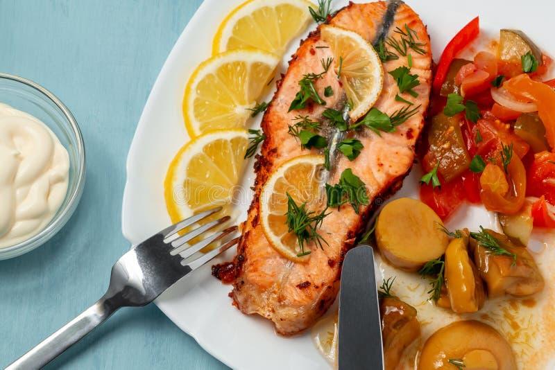 Medaglione di color salmone al forno del raccordo con insalata delle verdure e dei funghi marinati su un piatto bianco su un fond fotografie stock libere da diritti