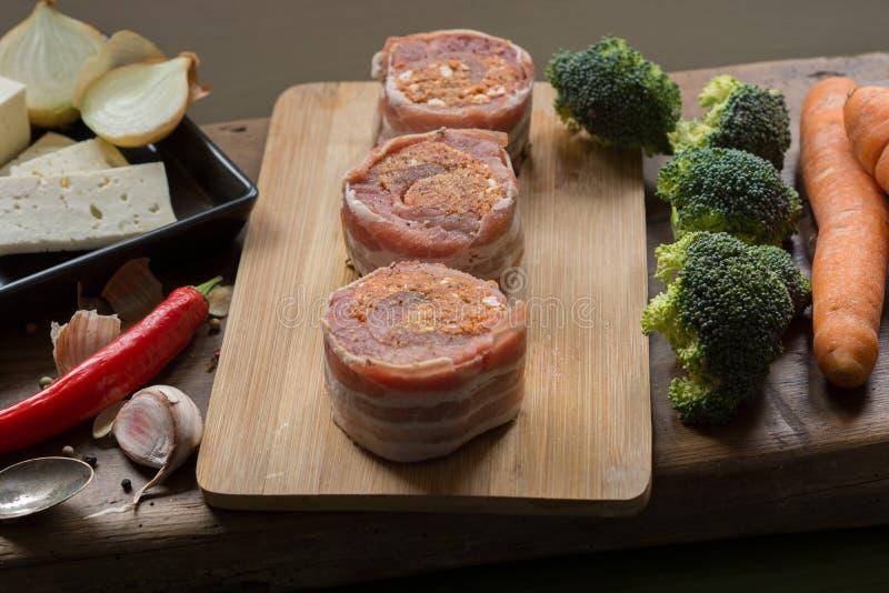 Medaglioni crudi del filetto di carne di maiale riempiti di salsiccia del chorizo ed avvolti con bacon immagine stock libera da diritti