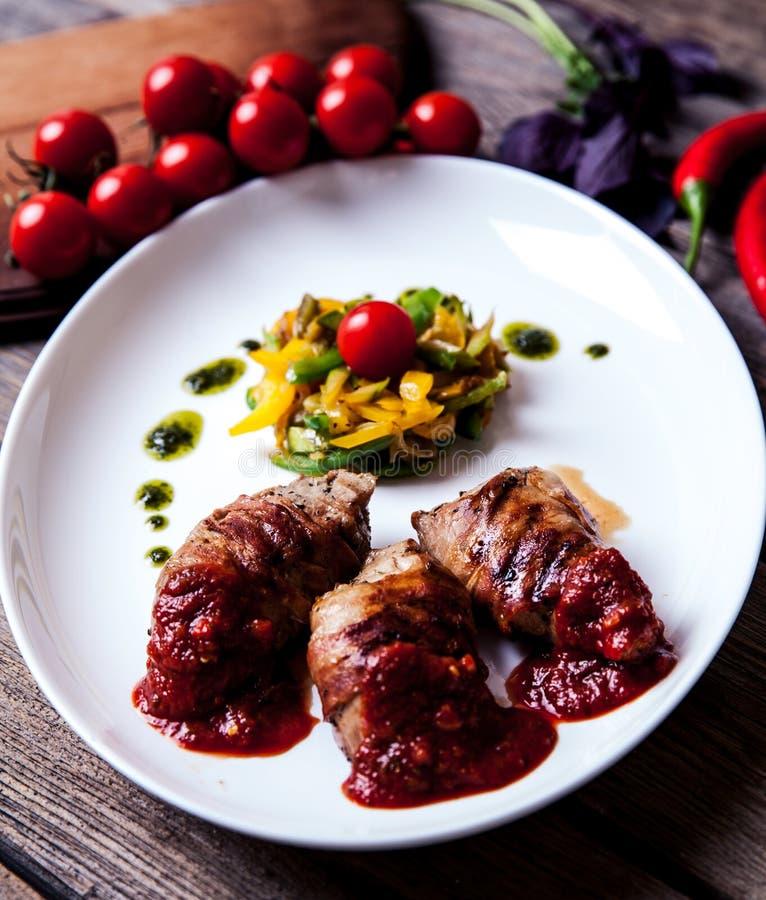 Medaglioni del vitello arrostito con un piatto laterale delle patate del gratin con i baccelli dei broccoli, dell'asparago e del  immagine stock libera da diritti