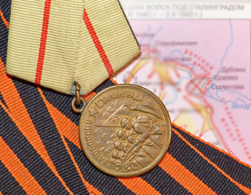 Medal `For the Defense of Stalingrad` on the background of the St. George`s ribbon and maps of the battle of Stalingrad. Awards of the soldier. Heirloom stock photo