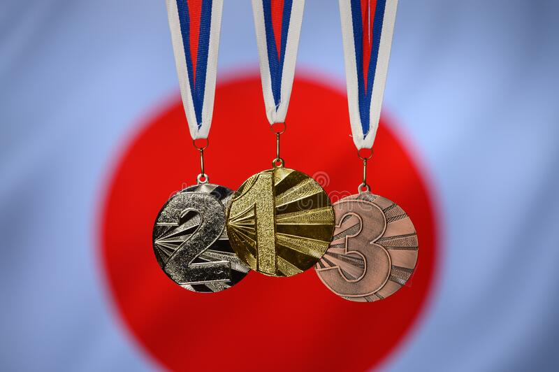 Medal set, gold silver and bronze, japan flag in background.  royalty free stock photo