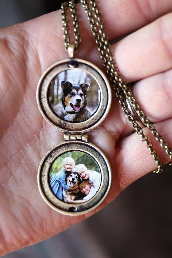 Medalhão antigo da terra arrendada da mão da mulher com as fotos das crianças e do cão de estimação para dentro fotografia de stock royalty free