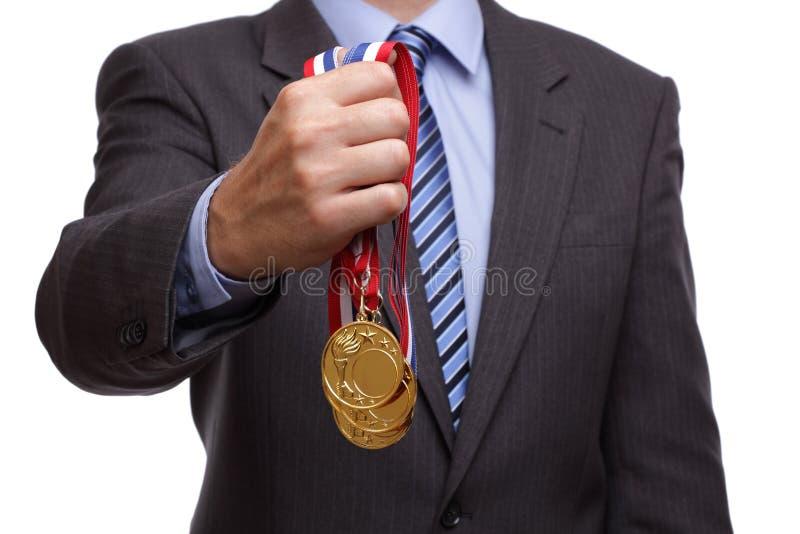 Medalha de ouro da terra arrendada do homem de negócios fotografia de stock royalty free