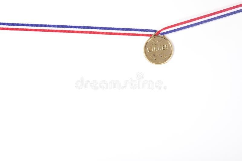 Medalla de oro en una cinta aislada en blanco imagenes de archivo