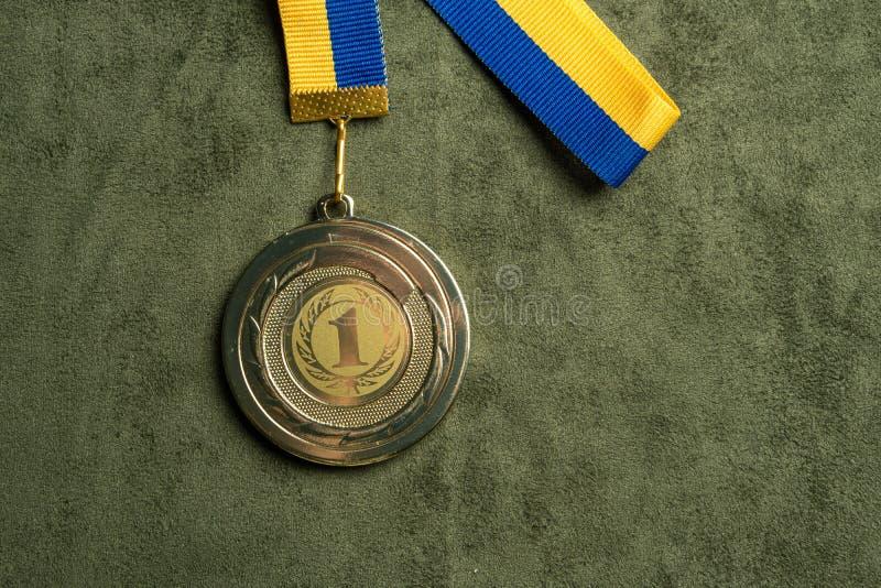 Medalla de oro para el primer lugar con la cinta amarilla y azul imagenes de archivo