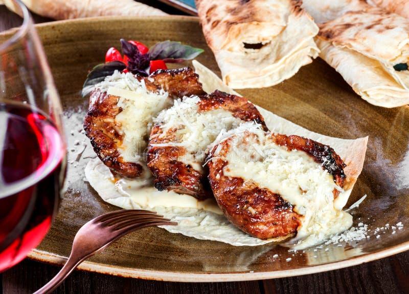 Medallones asados a la parrilla de la ternera del filete de la carne con la salsa y la copa de vino de queso en una placa fotos de archivo libres de regalías