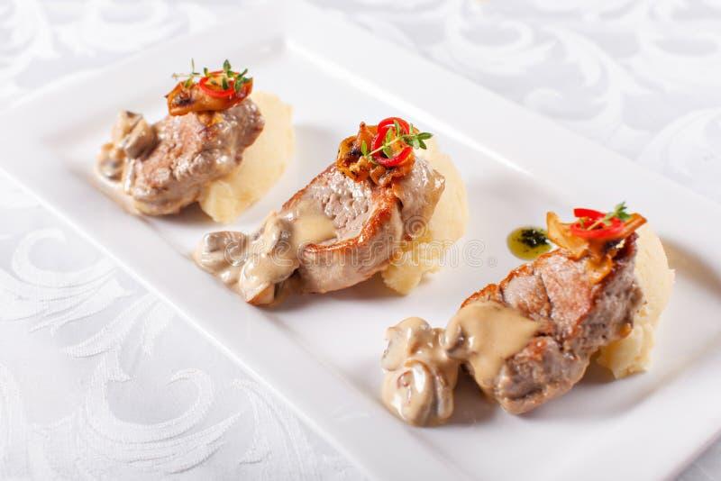 Medallones del cerdo con el puré de patata y las setas Filete de cerdo en una placa blanca, buen servicio La cena de boda con la  imagenes de archivo