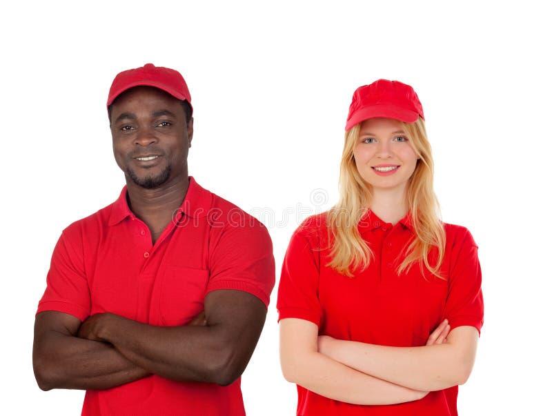 Medarbetare med deras röda likformig arkivfoto
