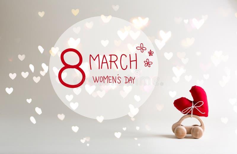 Meddelande för dag för kvinna` s med leksakbilen som bär en hjärta fotografering för bildbyråer