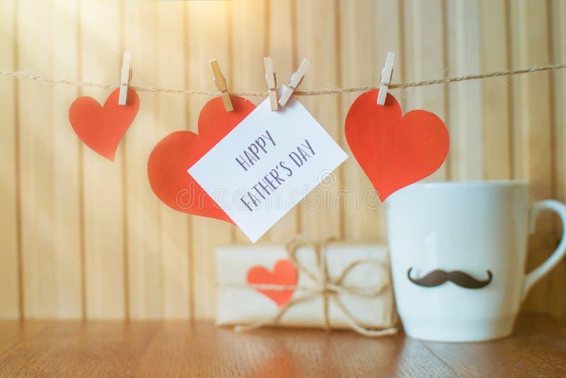 Meddelande för faderdag med pappers- hjärtor som hänger med klädnypor över träbräde arkivfoton