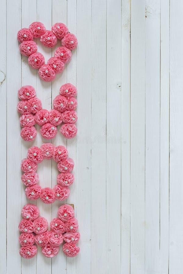 Meddelande för moderdag av rosa pappers- blommor över den vita trägalten royaltyfri bild