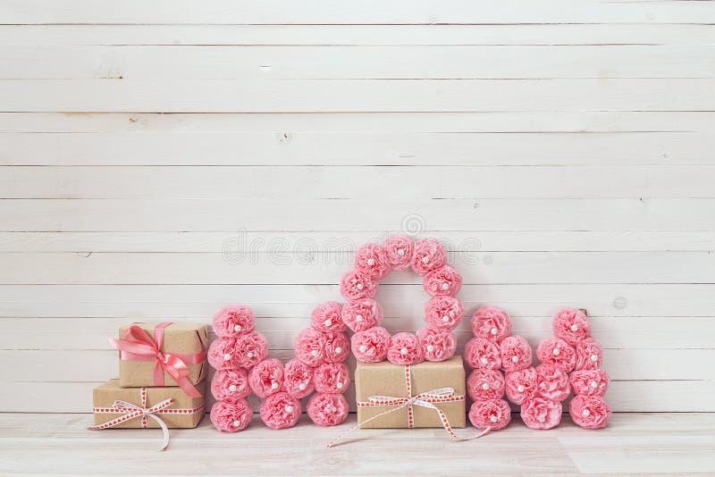 Meddelande för moderdag av rosa pappers- blommor över den vita trägalten arkivbilder