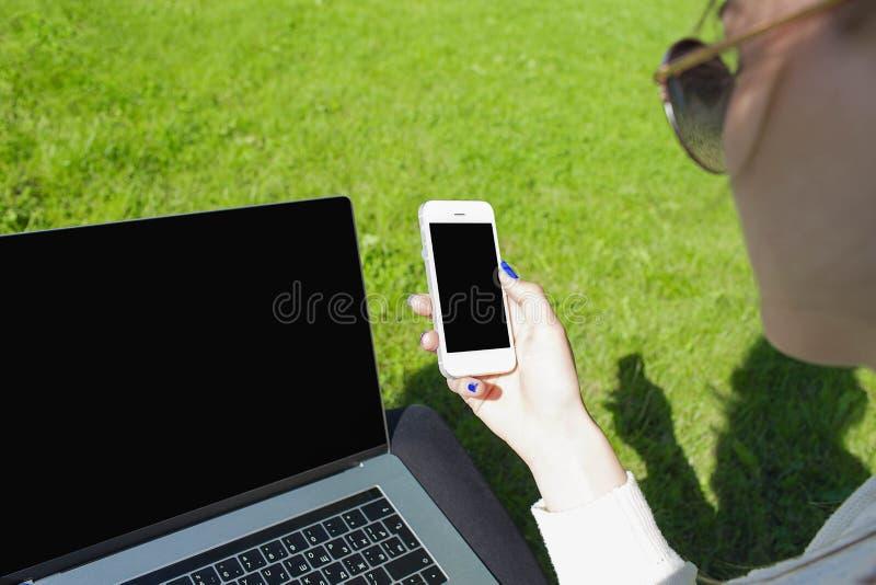 Meddelande för text för kvinnastudent läs- på celltelefonen, sammanträde på ett grönt gräs arkivbilder