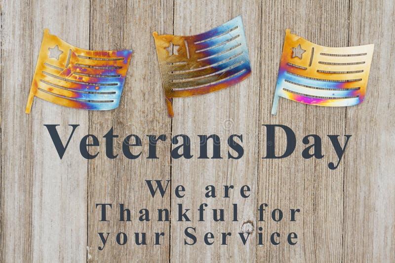 Meddelande för veterandag med metallflaggor på trä royaltyfria bilder