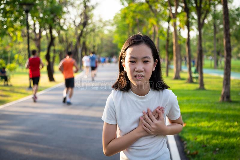 Meddelar tecknen av hjärtsjukdomen, den asiatiska lilla flickan med bröstkorgen smärtar omedelbart att lida från hjärtinfarkt eft royaltyfria foton