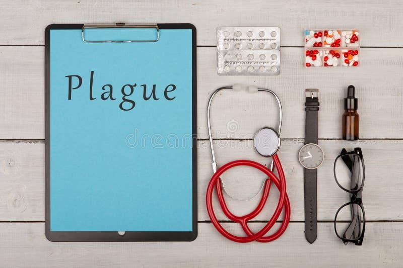 Medecine pojęcie - schowek z tekstem «dżuma «, pigułki, stetoskop, eyeglasses fotografia royalty free