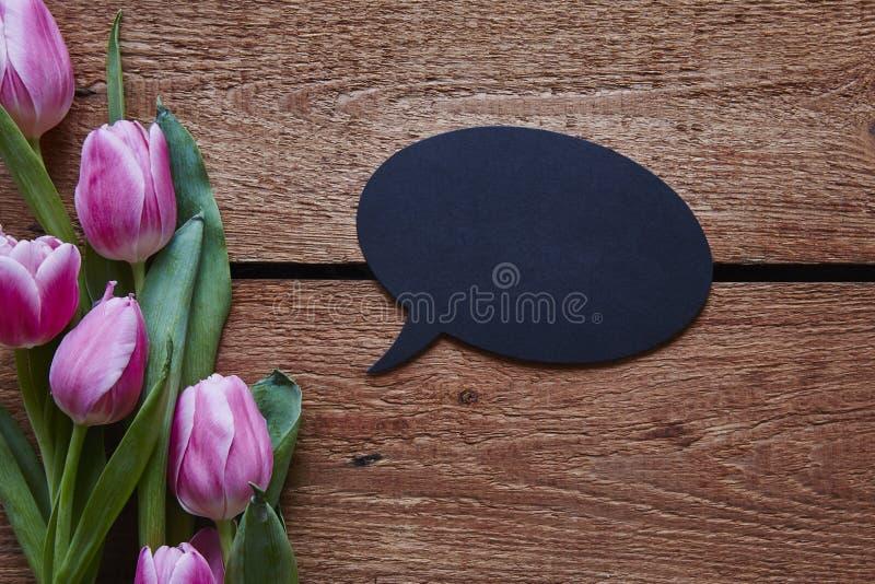 Mededeling in de bel van de de lentetoespraak en roze tulpen stock fotografie