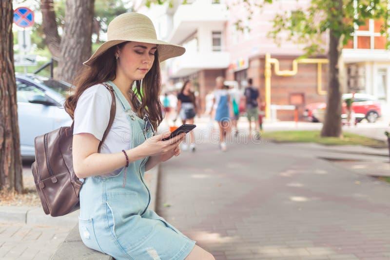 Mededeling Jonge en mooie vrouwenzitting in het Park en het gebruik de telefoon royalty-vrije stock afbeelding