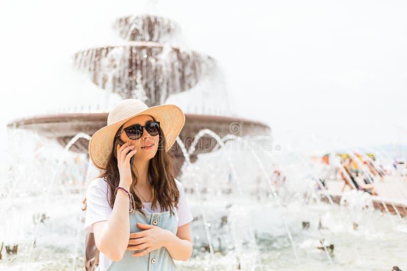 Mededeling Mooie jonge vrouw die in een hoed en glazen de telefoon uitnodigen Er is een fontein op de achtergrond stock foto